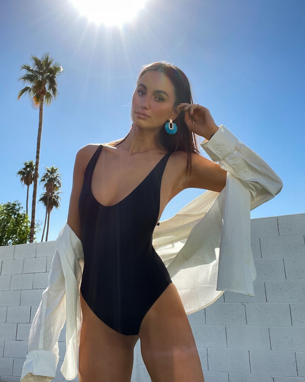 a woman wearing a black one piece swimsuit with a white button up shirt and turquoise fringe earrings with sun and palm trees in the background