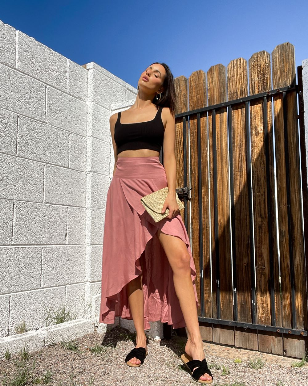 a woman with her face to the sun wearing a black crop top with a rose high low skirt and black slide sandals, holding a beige straw bag