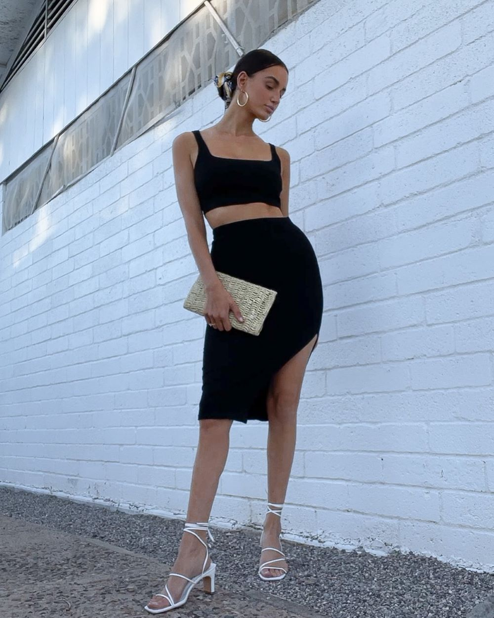 a woman wearing cute beach vacation outfit of black two piece dress with lace up white heels and a straw clutch