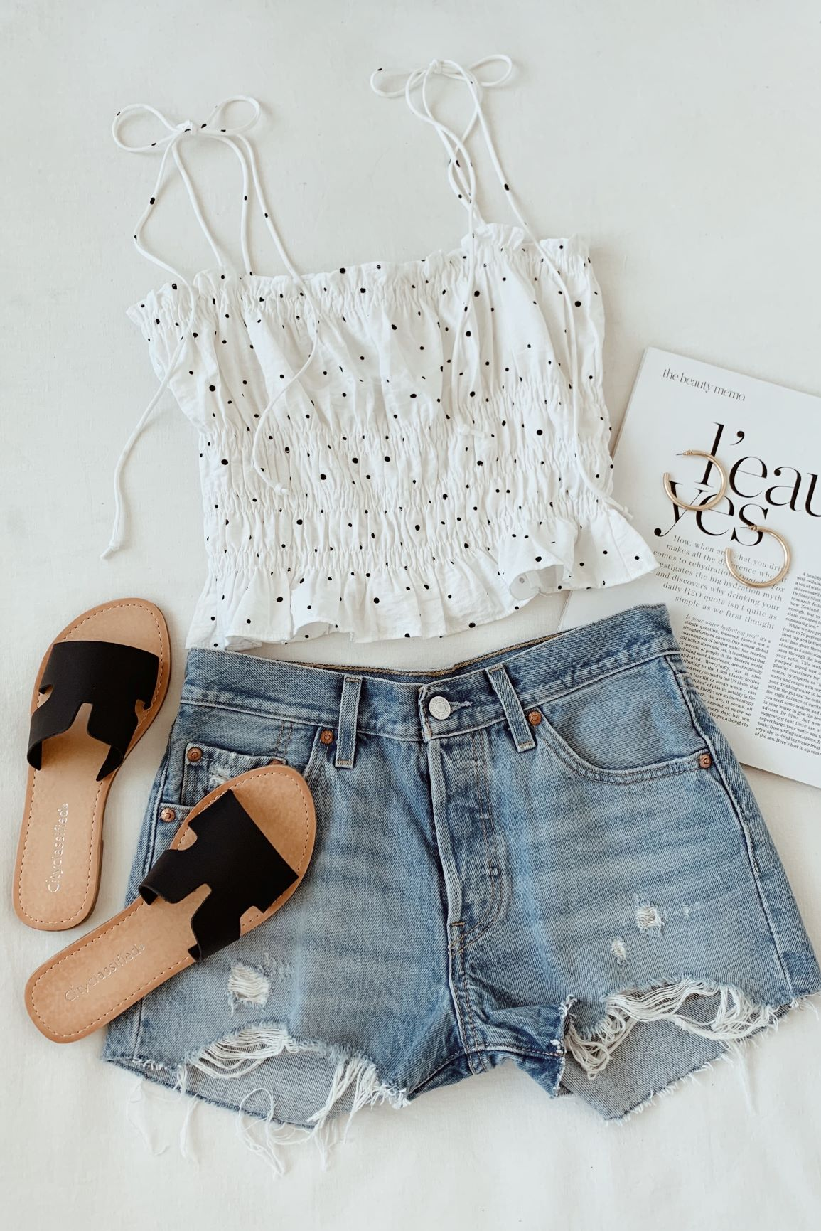white smocked top with polka dots paired with denim cutoff shorts and black slide sandals