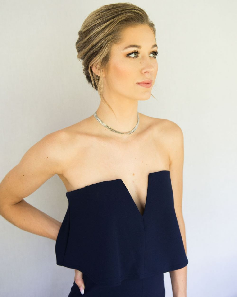 woman in navy strapless jumpsuit and french twist updo