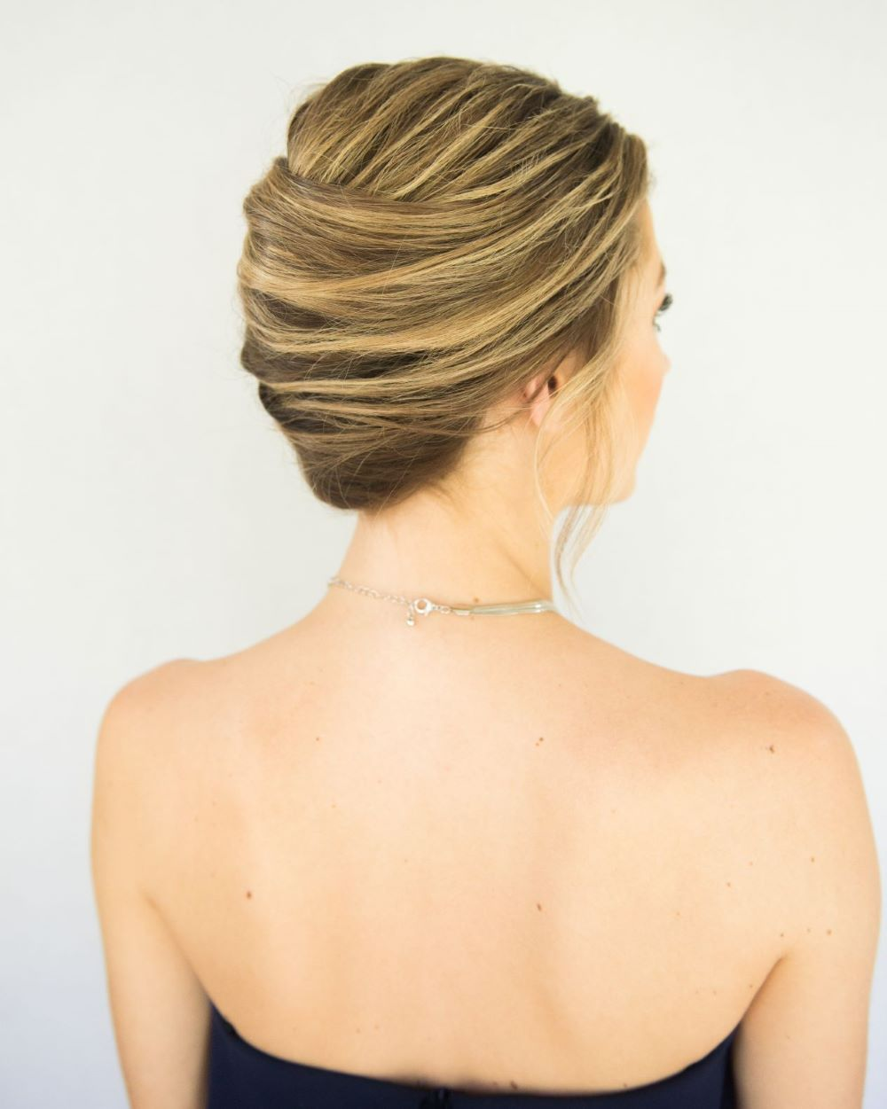 back view of woman wearing a french twist updo