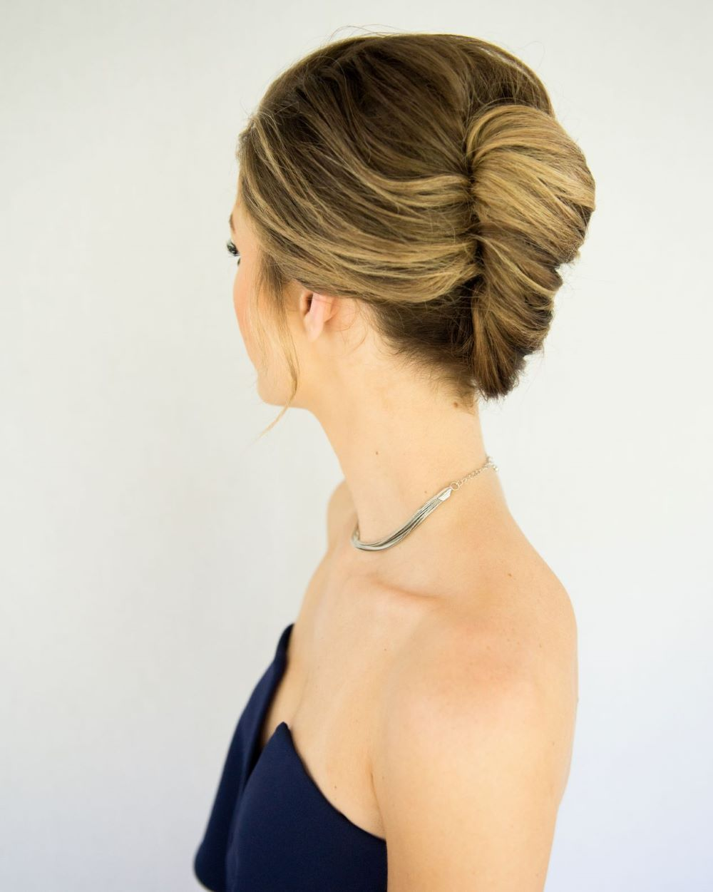 side view of woman wearing a french twist updo