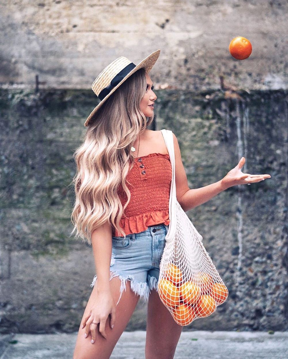 woman holding oranges wearing a rust orange smocked crop top and denim shorts with a hat