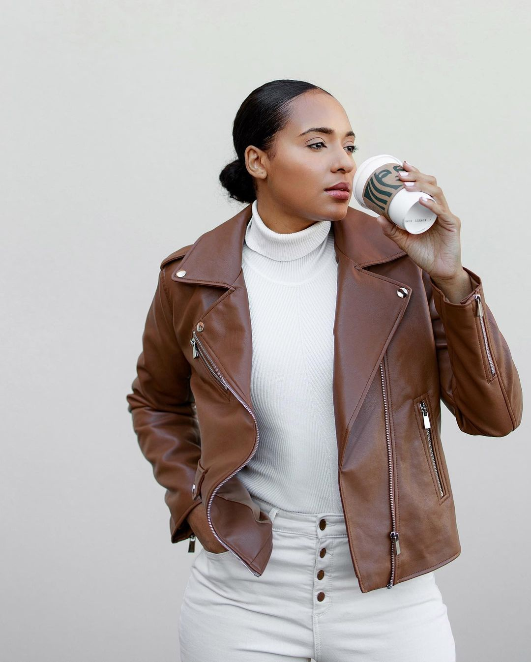a woman wearing a white outfit with a brown vegan leather moto jacket holding a starbucks coffee