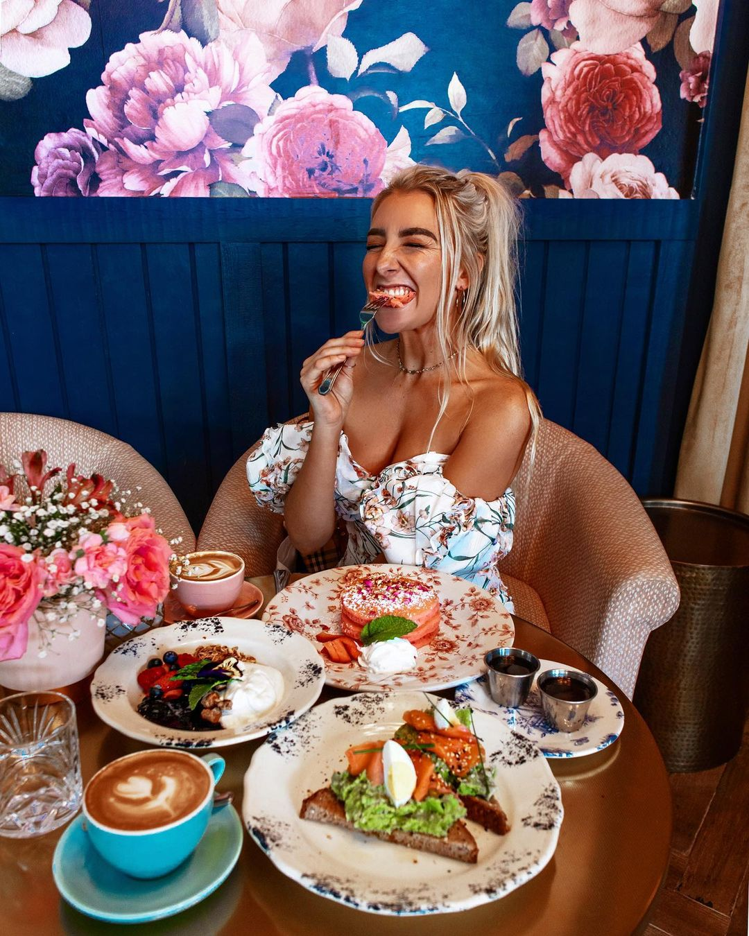 a woman in a floral outfit at a table full of food in a restaurant