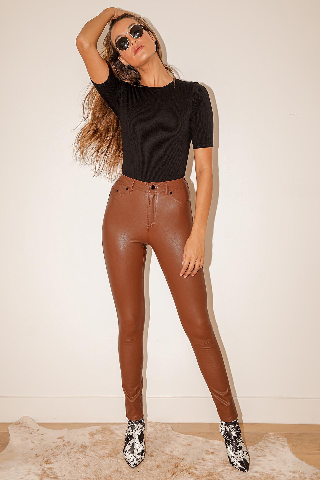 model in black tee and rust brown vegan leather pants