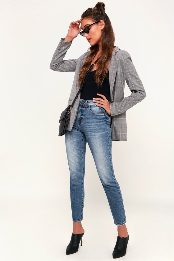 Pair the Tyler Medium Wash High Rise Mom Jeans with some mules for a classic look! These perfectly structured mom jeans look good with everything thanks to a faded, medium wash and a flattering high-waisted fit. Belt loops, hidden zip fly, branded top button, and five pocket cut. Skinny pant legs taper to an ankle length. Fit: This garment runs small - please size up. Length: Ankle length. Size 3 measures 37.75\