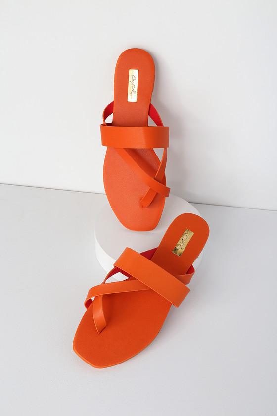 Slip into the Lizzy Orange Flat Sandals and let the vacay vibes roll! Soft vegan leather starts at a toe-thong upper that carries into a strappy vamp with a slide-on design perfect for pairing with your new sundress. 0. 25\
