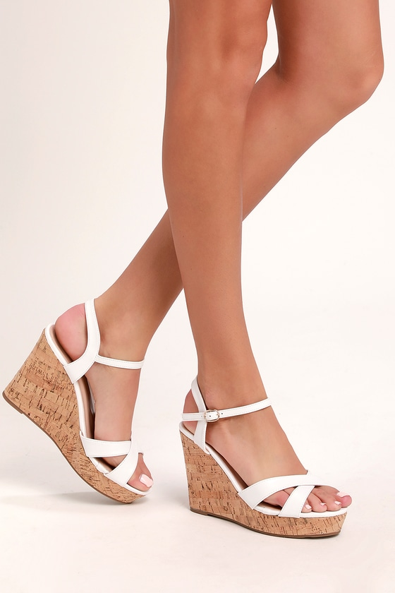 Salty air, sun-kissed hair and the Lulus Nixie White Wedge Sandals are the best parts of vacation! White vegan leather straps crisscross over a cute peep-toe and shapes a matching quarter strap that secures around the ankle with a silver buckle. A cork-wrapped 1\