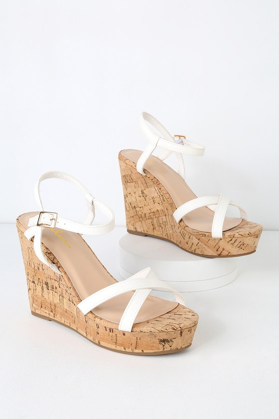 Pair the Lulus Darlene White Wedge Sandals with your fave sundress for a cute and classic look! Vegan leather shapes slender, crisscrossing straps over a peep-toe as well as a matching quarter strap that secures around the ankle with a gold buckle. A cork-wrapped 1\