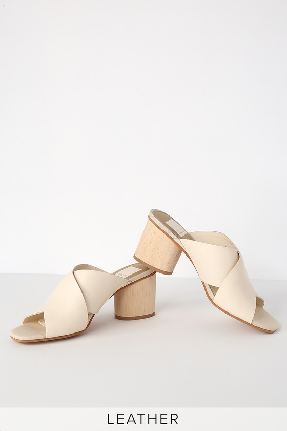 The Dolce Vita Atira Ivory Leather Peep-Toe Mules pair perfectly with a chic swim cover-up and a fruity cocktail! Soft, genuine leather shapes a crisscrossing peep-toe upper, and slide-on design, all atop a chic wooden block heel. 2. 5\