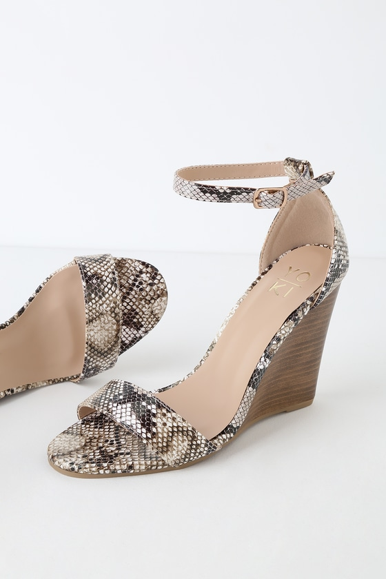 Tired of your boring everyday sandals? Get a fresh new look with the Ramona Snake Wedge Sandals! Snake embossed vegan leather shapes these chic wedges with a slender toe-strap. Adjustable strap (with gold buckle) wraps around the ankle and has a matching heel cup. 4\