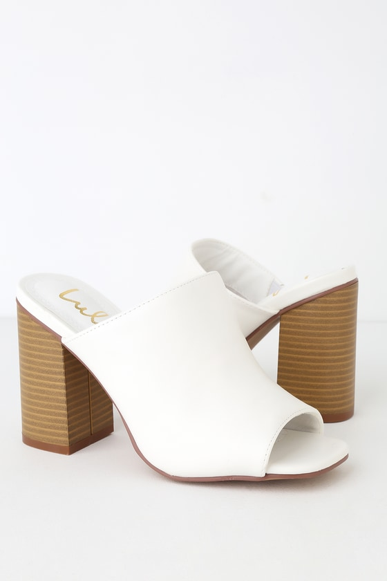 Lulus Exclusive! We are loving the Lulus Raelynn White Peep-Toe Mules styled with so many different looks! From casual to dressy these trendy mules are sure to please with their peep-toe upper atop a sturdy, stacked block heel. The vegan leather can be dressed up or down depending on the occasion. Fit: This garment fits true to size. 4\
