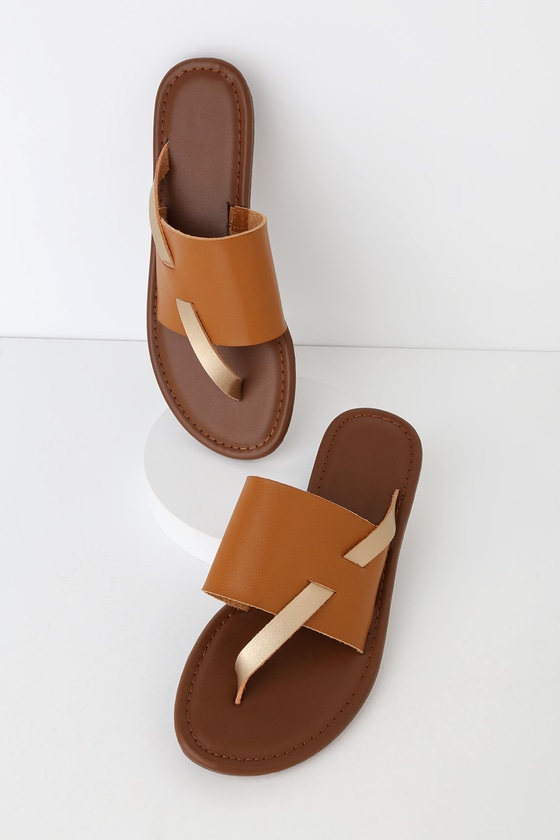 The Finlay Tan Thong Sandals are a modern twist to your favorite thong sandals you never knew you needed! These trendy sandals feature a tan, wide strap upper and thin gold asymmetrical toe thong strap that crosses the vamp. These simply adorable sandals will pair perfectly with a crop top and some palazzo pants! 0. 5\