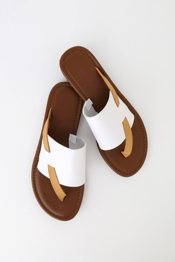 The Finlay White Thong Sandals are a modern twist to your favorite thong sandals you never knew you needed! These trendy sandals feature a white, wide strap upper and thin tan asymmetrical toe thong strap that crosses the vamp. These simply adorable sandals will pair perfectly with a crop top and some palazzo pants! 0. 5\