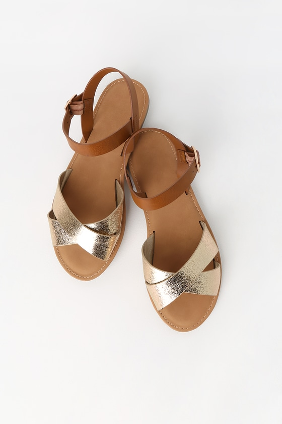The Vine Gold Flat Sandals are a warm-weather staple! A textured, shiny gold crisscrossing toe strap tops these classic flat sandals with a contrasting adjustable brown quarter strap and gold buckle. 0. 25\