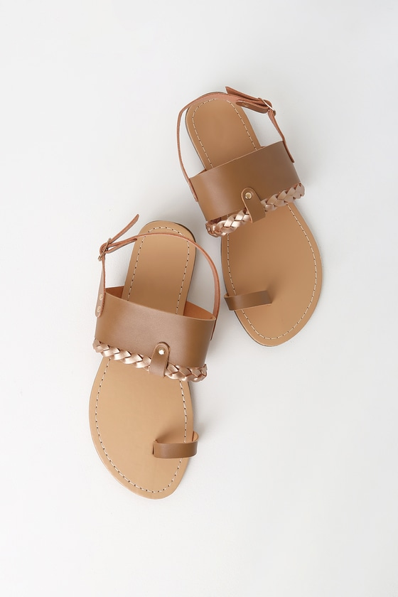 The Trinity Tan Flat Sandals are the perfect addition to a pair of denim shorts! Smooth vegan leather creates a toe-loop upper, and vamp strap with a contrasting gold braided accent. Gold back strap secures with a matching shiny gold buckle. 0. 25\