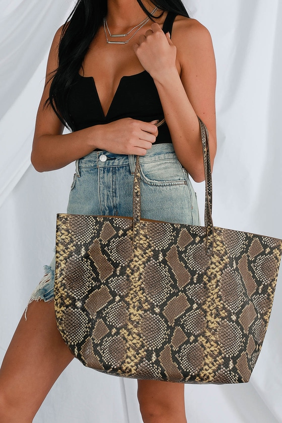 Nothing else makes us swoon quite like the Lulus Charmer Brown Snake Print Tote! Sleek, snake-embossed vegan leather shapes a wide, oversized tote bag with a spacious interior and a bonus mini bag with a zip closure. Mini bag is lined. Bonus mini bag measures 12\