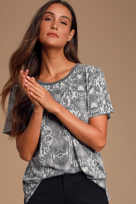 Travel the world in style with the Free People Tourist Beige Snake Print Tee! This tunic-length tee, made from ultra-soft, burnout jersey-knit fabric, features a washed snake print, in shades of beige, grey, and black, across the relaxed, short sleeve bodice. Grey ribbed knit trims the rounded neckline, while raw hems and stitching create the perfect worn-in look. Pair with your favorite denim and sandals for an effortless and chic look! Fit: This garment fits true to size. Length: Size small measures 26.5\