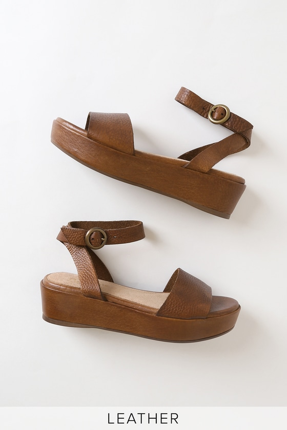 We can\'t wait to wear the Seychelles Monogram Tan Leather Flatform Sandals everywhere! Pebbled, genuine leather shapes these chic shoes with a cute peep-toe upper and matching ankle strap that wraps and secures around the ankle with an antiqued gold, round buckle. A sleek flatform silhouette adds a little extra height. 1. 75\