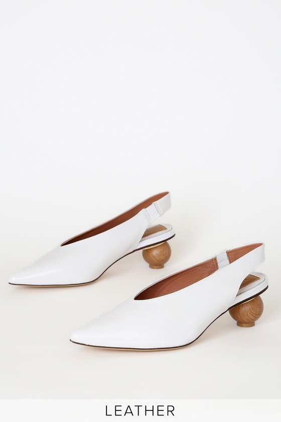 Step into an elevated state of fashion with the Jaggar Spheric Ivory Patent Leather Slingback Pumps! Chic white patent leather, with texturing throughout, shapes these pointed-toe pumps with with an elasticized slingback strap and sculpted, wood-look heel. Available in Euro sizes only. 2\