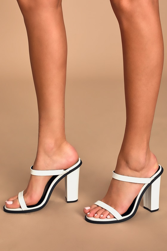 Keep it simple and chic in the Carmona White High Heel Sandals! These cute sandals feature slender toe straps and matching vamp straps atop a single-sole silhouette, all composed of smooth white vegan leather. Contrasting black sole and trim adds an edgy vibe, while chunky block heel makes for comfy, all day wear. Slide-on design. 4. 25\