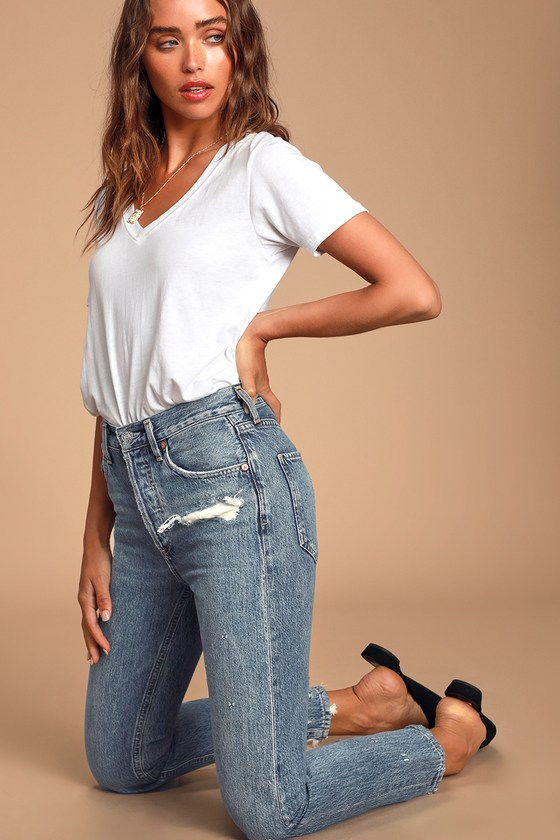 The AGOLDE Jamie Medium Wash Hi Rise Classic Raw Hem Jeans are an essential cool-girl piece! Thick, medium wash denim (in AGOLDE\'s Grade wash) shapes a high-rise fit with belt loops, five-pocket cut, and button fly with branded top button. Whiskering and distressing decorate the tapered pant legs and raw, shredded, cropped hems. Fit: This garment fits true to size. Length: Size 26 measures 37.5\