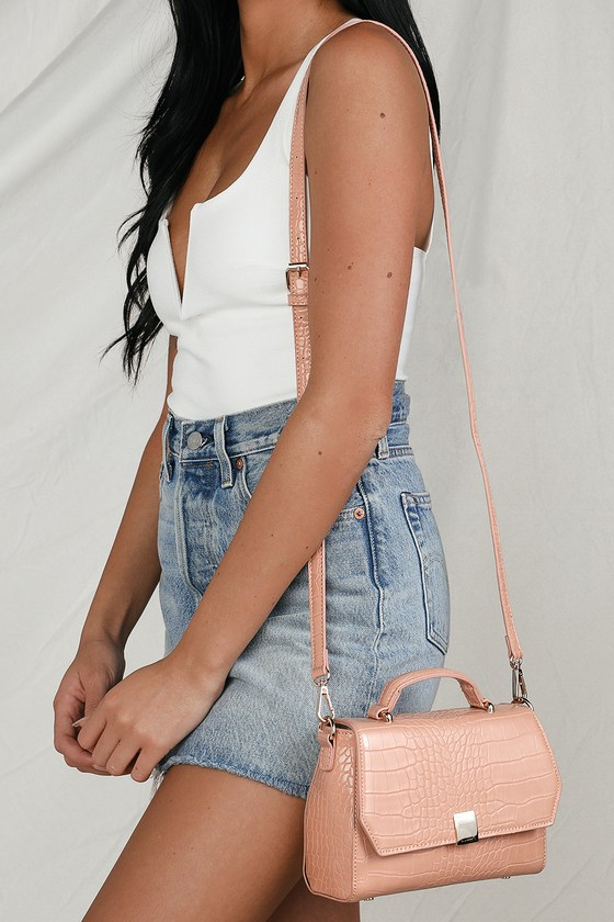 The Lulus Carlotti Blush Pink Crocodile Embossed Handbag is the perfect present to yourself! This trendy crocodile embossed purse, made from vegan leather, is ideal for bringing all of your glam girl essentials everywhere you go! Open the magnetic closure to reveal a structured interior with two sidewall pockets. Carry by the charming tote handle or throw over your shoulder with the adjustable crossbody strap. Gold hardware adds an ultra-luxe vibe throughout! Fully lined. Bag measures 8. 25\