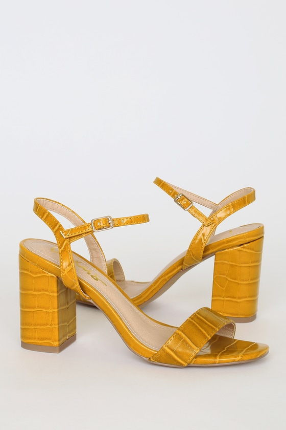 Lulus Exclusive! Dress them up or down, the Lulus Arya Mustard Croc High Heel Sandals can do it all! Crocodile-embossed vegan leather shapes a peep-toe upper and a slender quarter strap with gold buckle. 3. 5\