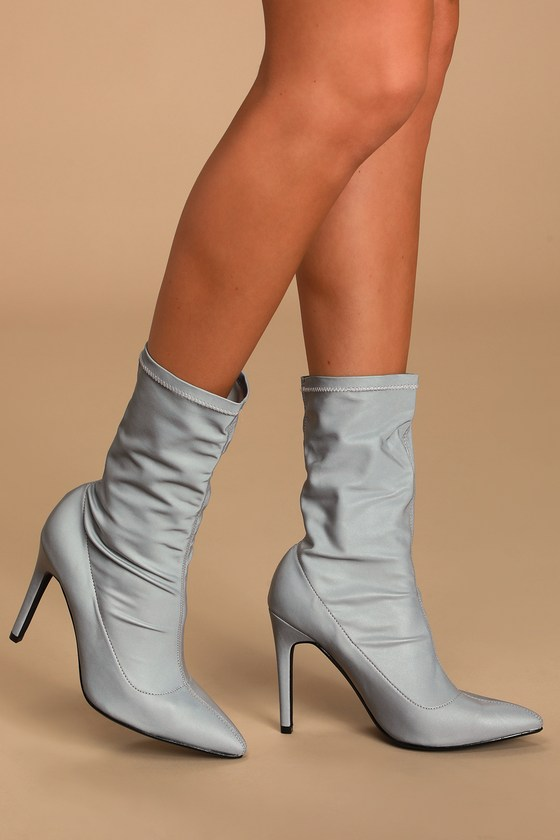 Shine so bright that the haters can\\\'t see you in the Lemon Drop by Privileged Alessey Silver Reflective Mid-Calf High Heel Sock Boots! These unique sock boots are shaped by a stretchy, reflective material (that glows in bright light) that forms a classic pointed-toe upper, mid-calf shaft, and stiletto heel. Pull on design makes for easy on and off. Throw these boots on for an Insta-worthy night out on the town! 4. 25\\\