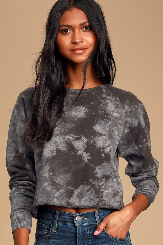 Some days you just gotta\' get comfy and chill; the Ética Yara Washed Black and Grey Tie-Dye Pullover Cropped Sweatshirt is there for you on days like that! Soft, French terry, with a cool black and grey tie-dye print, shapes this sweatshirt featuring a classic crew neckline, long raglan sleeves, and a wide-cut boxy bodice with a cropped, raw hem. Ribbed knit accents the neck, sleeves, and sides of the bodice. Made with fair labor practices and environmentally conscious manufacturing, using 99% less water, 63% less energy, and 70% fewer chemicals than the rest of the industry. Fit: This garment fits true to size. Length: Size small measures 19.5\
