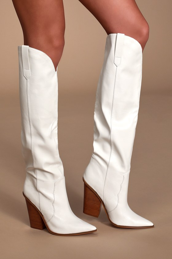 Stand tall and stand out in the Steve Madden Ranger White Western Knee-High Boots! Sleek vegan leather creates a pointed-toe upper, Western-inspired vamp, and knee-high shaft. A notched collar with pull tabs at both sides completes these essential boots. 4\