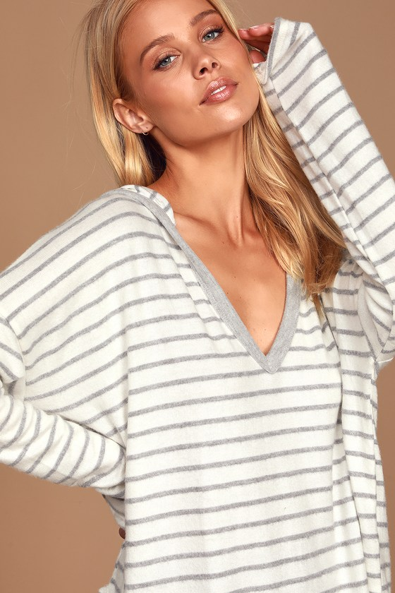 Lulus Exclusive! Look and feel your absolute best in the Lulus Act Casual White and Grey Striped Hoodie! Soft and stretchy knit fabric, covered in cute grey stripes, shapes this essential hoodie that features a V-neckline (with a hood), long sleeves, and a relaxed-fit, oversized bodice that ends in a high-low, rounded hem. Fit: This garment fits true to size. Length: Size small measures 26.5\