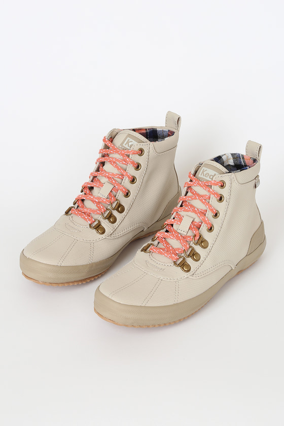 The Keds Scout II Matte Twill Taupe Lace-Up Ankle Boots are trendy and practical! Sleek water and stain resistant twill shapes these sturdy ankle boots with a seamed, rounded toe upper, and lace-up vamp, with cute coral pink laces. Back pull tab and logo tags at tongue, outstep, and back. Navy Blue and coral pink plaid fleece lined shaft. Fit: This garment fits true to size. 1\
