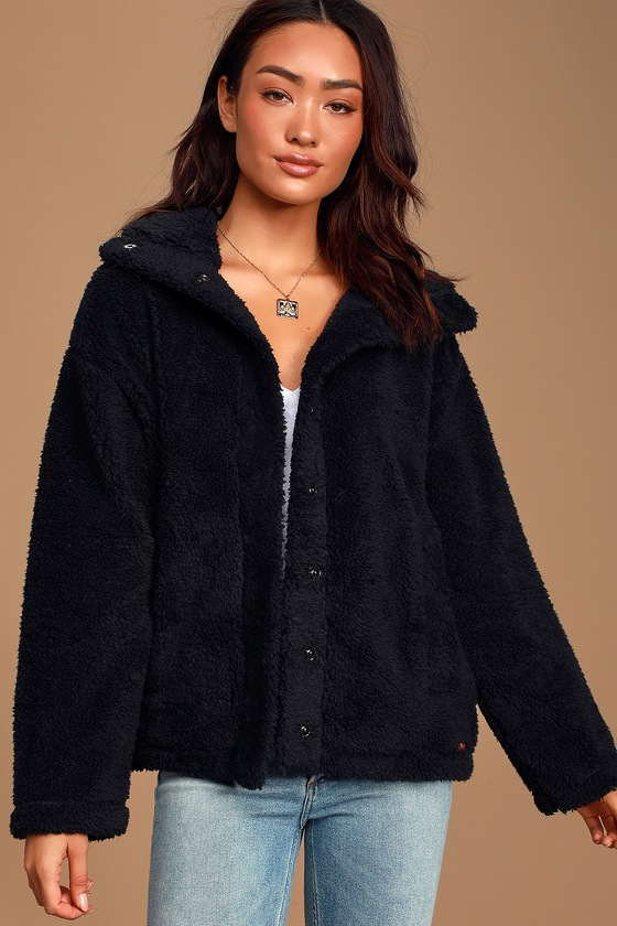 Cozy has never looked cuter now that we\'ve met the Billabong Cozy Days Black Sherpa Jacket! Super soft faux sherpa shapes this trendy jacket with a collared neckline and hidden snap button placket. Long sleeves, with drop shoulders, frame the relaxed bodice featuring two vertical, welted pockets. Leather logo tag at front hem. Fit: This garment fits true to size. Length: Size small measures 25\