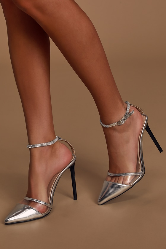 You\'re going to look stunning in the Bebo Kady Clear and Silver Rhinestone Pointed-Toe Heels! Sleek, metallic vegan leather shapes a trendy pointed-toe upper, with a clear vinyl strip, and an adjustable ankle strap that is adorned with rhinestones and a shiny silver buckle. Slender stiletto heel gives these heels a modern vibe! Available in Euro sizes only. 4. 5\