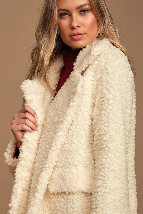 Cozy has never looked cuter now that we\'ve met the Divine Comfort Cream Teddy Jacket! Fuzzy faux fur fabric shapes this incredibly cute jacket with a collared neckline and long lapels that lead into a boxy bodice with a hook and eye closure. Long cozy sleeves. Twin front flap pockets are perfect for stashing your daily essentials. Pair with cropped denim for a perfectly trendy look! Fit: This garment fits true to size. Length: Size small measures 25\
