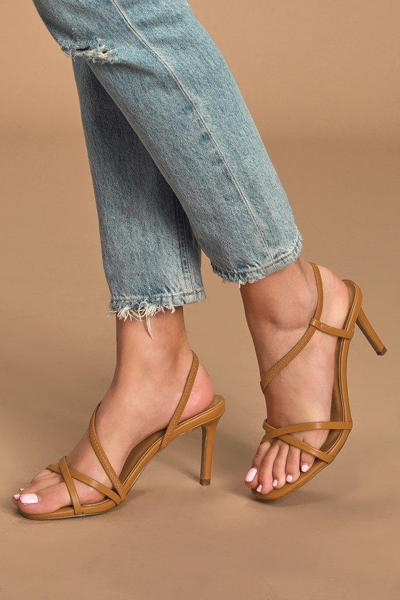 Awaken your inner boss babe in the Lulus Byrdie Brown Strappy High Heel Sandals! Vegan leather shapes a sleek single sole silhouette with an open, square-toe upper, framed by crisscrossing toe straps. Elastic strap sprouts from vamp and wraps into a secure slingback, creating an asymmetrical design. 3. 25\