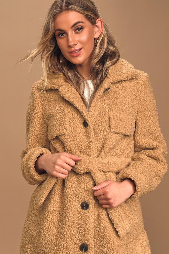 Promises of comfort and style are kept by the Blank NYC Here To Stay Tan Belted Sherpa Coat! Soft faux Sherpa shapes this ultra-cozy coat with a collared neckline and button-front bodice with twin faux top flap pockets. Long sleeves frame the oversized silhouette while a tying belt and notched, rounded hem. Hidden side seam pockets. Fit: This garment fits true to size. Length: Mid-thigh. Size small measures 33.5\