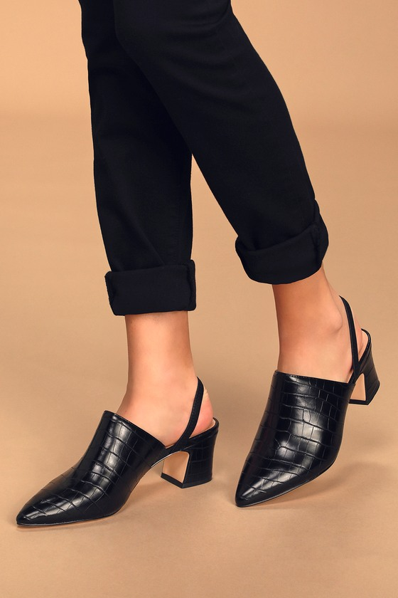 Step up your shoe game and your look with the Chinese Laundry Paulo Black Crocodile Embossed Pointed-Toe Slingback Mules! Sleek crocodile embossed vegan leather shapes these chic mules with a pointed-toe upper, elastic slingback strap, and block heel. Elastic gusset at instep creates a custom fit. Fit: This garment fits true to size. 2. 5\\\