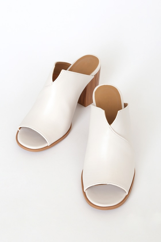 Everyone will be asking you for styling tips after they see you in the Bette Off White Peep-Toe Mules! Sleek vegan leather overlaps to create the peep-toe upper of these cute heels with a notched collar and chunky block heel. Slide-on design. Fit: This garment fits true to size. 3\