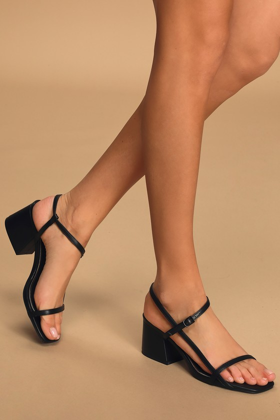 Your new summer dress isn\\\'t complete without the Lilith Black High Heel Sandals! Vegan leather shapes these chic heels that feature an open toe upper, with a square toe and slender toe band. A matching long strap starts at the toe bed and wraps into an adjustable quarter strap, secured with a matching black buckle. Fit: This garment fits true to size. 2. 5\\\