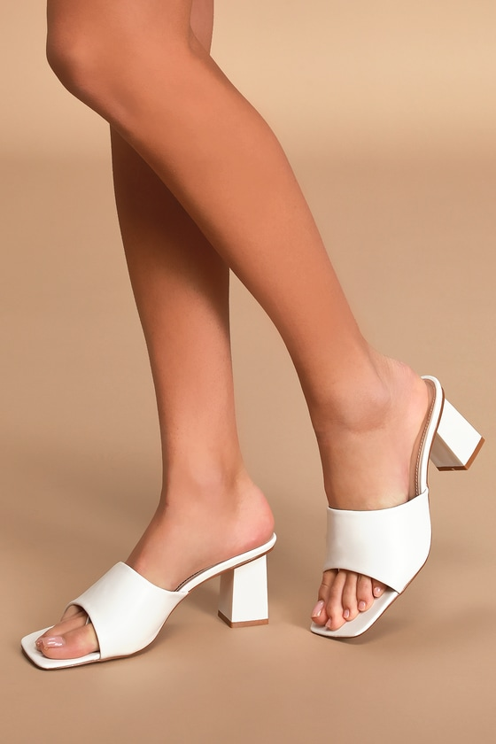 A classic romance with a modern twist describes the Raid Pia White Peep Toe Mules to a T! Sleek vegan leather shapes a peep-toe upper, a square toe bed with a discreet thong toe strap, and a wide vamp atop a sculpted square block heel. Available in Euro sizes only. Fit: This garment fits true to size. 2. 5\
