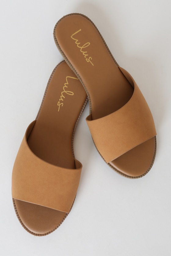 Step into summer with the Reina Tan Nubuck Slide Sandals! Soft vegan nubuck shapes a wide, slightly asymmetrical toe band atop a peep-toe upper. Easy to wear slide-on-design. Fit: This garment fits true to size. 0. 5\\\