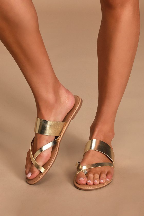 Stroll along sandy shores in style with the Oceanfront Gold Flat Sandals! Smooth vegan leather starts at a crisscrossing toe-thong upper, then carries into a strappy vamp with a slide-on design. Pair these simple slides with everything from distressed shorts to sundresses! Fit: This garment fits true to size. 0. 25\\\