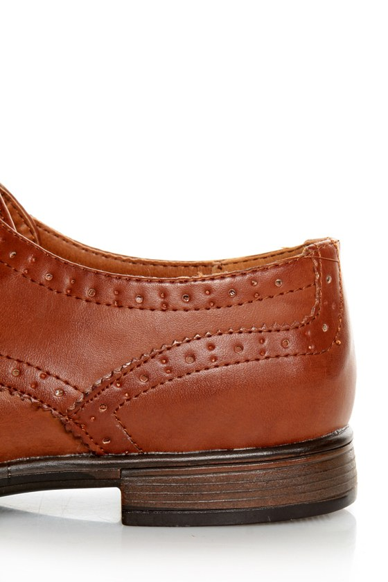 The Dollhouse Trickster Chestnut Brogue Lace-Up Oxfords are the quickest trick to a flawless \\\\\\\'fit! Tan vegan leather oxfords with brogue details and coated shoestrings.